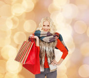 Smiling young woman with red shopping bags Royalty Free Stock Image