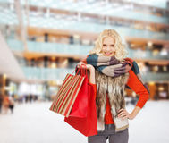 Smiling young woman with red shopping bags Royalty Free Stock Images