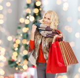 Smiling young woman with red shopping bags Royalty Free Stock Photos