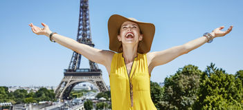 Smiling young woman rejoicing in front of Eiffel tower in Paris royalty free stock photography