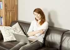 Smiling young woman relaxing with her laptop Stock Photos