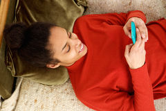 Smiling young woman relaxing at home with mobile phone Royalty Free Stock Photography