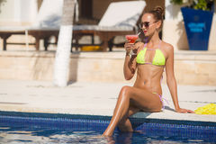 Smiling young woman relaxing in pool with cocktail. stock images