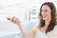 Smiling young woman with remote control sitting on sofa Royalty Free Stock Photo