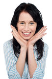 Smiling young woman resting her chin over palms Royalty Free Stock Image