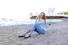 Smiling young woman rests on beach and poses in camera, sitting Royalty Free Stock Images