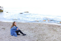 Smiling young woman rests on beach and poses in camera, sitting Stock Image