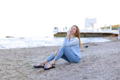 Smiling young woman rests on beach and poses in camera, sitting Stock Photos