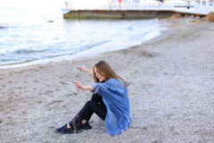 Smiling young woman rests on beach and poses in camera, sitting Royalty Free Stock Photos