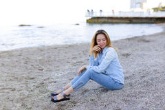 Smiling young woman rests on beach and poses in camera, sitting Royalty Free Stock Image