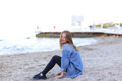 Smiling young woman rests on beach and poses in camera, sitting Stock Photography