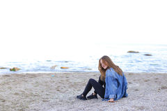 Smiling young woman rests on beach and poses in camera, sitting Stock Images