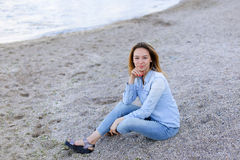 Smiling young woman rests on beach and poses in camera, sitting Stock Photo