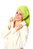 Smiling young woman in a robe with towel on her head on white ba Royalty Free Stock Photo