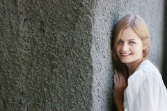 Smiling young woman and rough wall Stock Photos