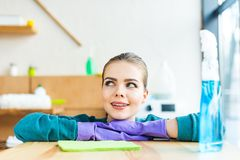 Smiling young woman in rubber gloves looking away. At home Royalty Free Stock Photo