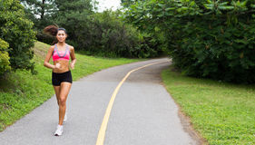 Smiling young woman running for fitness Royalty Free Stock Photography