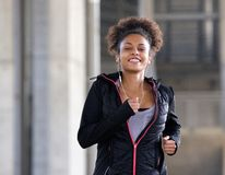 Smiling young woman running outdoors with earphones Stock Images