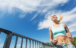 Smiling young woman running outdoors Royalty Free Stock Image