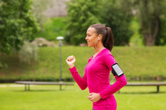 Smiling young woman running outdoors Royalty Free Stock Images