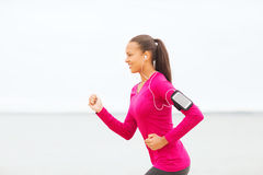 Smiling young woman running outdoors Royalty Free Stock Photo