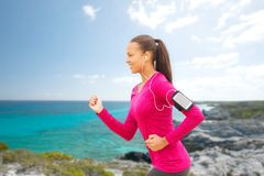 Smiling young woman running outdoors Stock Photography