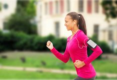 Smiling young woman running outdoors Stock Image