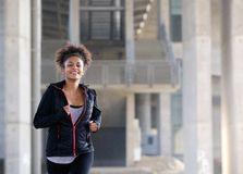 Smiling young woman running outside Stock Images