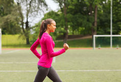 Smiling young woman running on track outdoors Stock Image