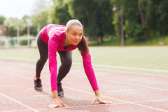 Smiling young woman running on track outdoors. Fitness, sport, training and lifestyle concept - smiling african american woman running on track outdoors Royalty Free Stock Photography