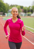 Smiling young woman running on track outdoors. Fitness, sport, training and lifestyle concept - smiling african american woman running on track outdoors Stock Image