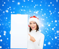 Smiling young woman in santa hat with white board Stock Photo