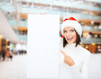 Smiling young woman in santa hat with white board Royalty Free Stock Images