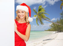 Smiling young woman in santa hat with white board Stock Images