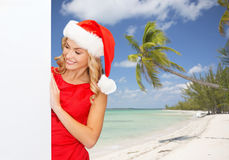 Smiling young woman in santa hat with white board Royalty Free Stock Image
