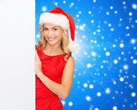 Smiling young woman in santa hat with white board Stock Photos