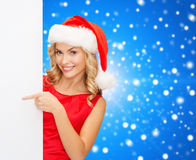 Smiling young woman in santa hat with white board Stock Image