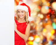 Smiling young woman in santa hat with white board Royalty Free Stock Photos