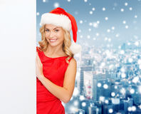 Smiling young woman in santa hat with white board Royalty Free Stock Photography