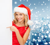 Smiling young woman in santa hat with white board Royalty Free Stock Photo