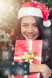 Smiling Young woman in santa helper hat with gift box royalty free stock photography
