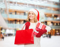 Smiling young woman in santa helper hat with gifts Royalty Free Stock Image