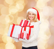 Smiling young woman in santa helper hat with gifts Stock Photography