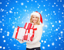 Smiling young woman in santa helper hat with gifts Stock Image