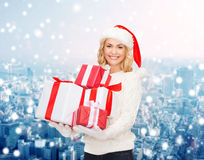 Smiling young woman in santa helper hat with gifts Royalty Free Stock Photos