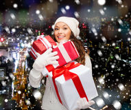 Smiling young woman in santa helper hat with gifts Stock Photo