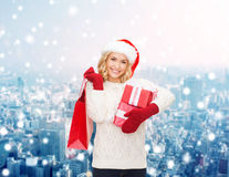 Smiling young woman in santa helper hat with gifts Royalty Free Stock Photography