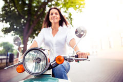 Smiling young woman on a scooter Royalty Free Stock Photo