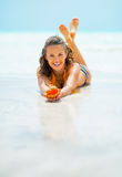 Smiling young woman on sea shore and showing shell Stock Image