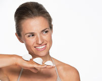 Smiling young woman with seashells looking on copy space Royalty Free Stock Image